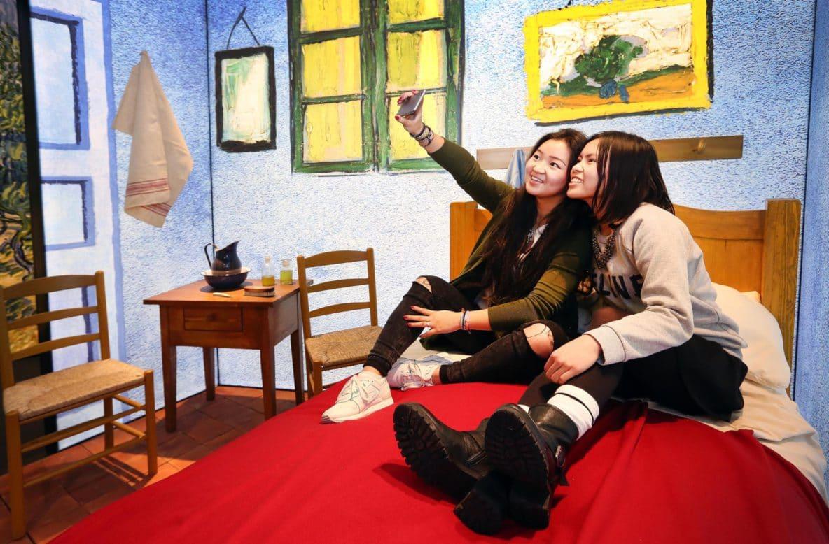 mulheres tiram selfie no quarto da exposição Meet Vincent Van Gogh