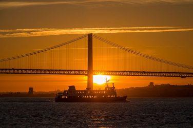 barco no rio tejo com pôr-do-sol