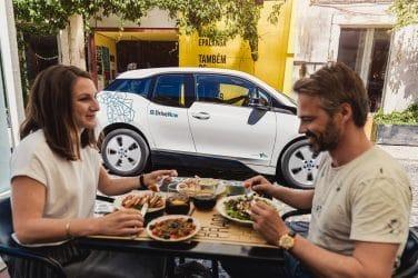 casal a almoçar frente ao DriveNow BMW i3