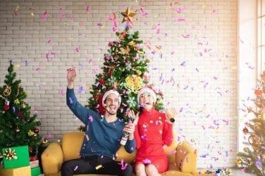 man-and-woman-wearing-santa-hats-sitting-on-sofa-popping