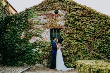 casal de noivos frente a uma casa arbórea