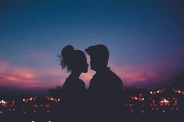 casal de namorados com luzes da cidade ao fundo