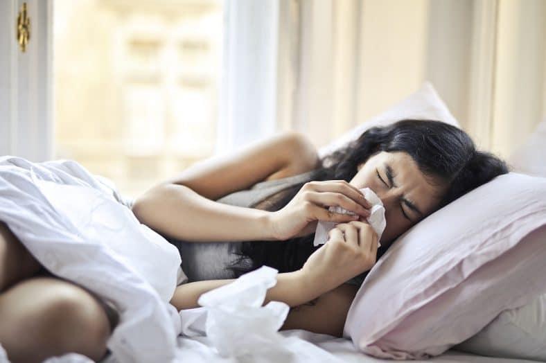 mulher a espirrar com possíveis sintomas de covid-19