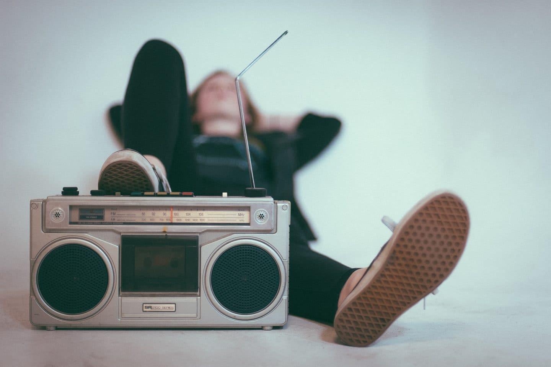 homem a ouvir rádio deitado na cama