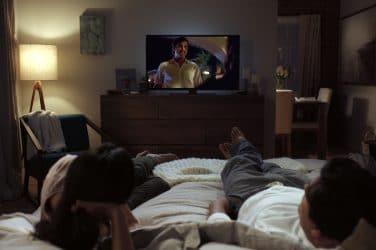 casal deitado na cama a assistir séries na netflix