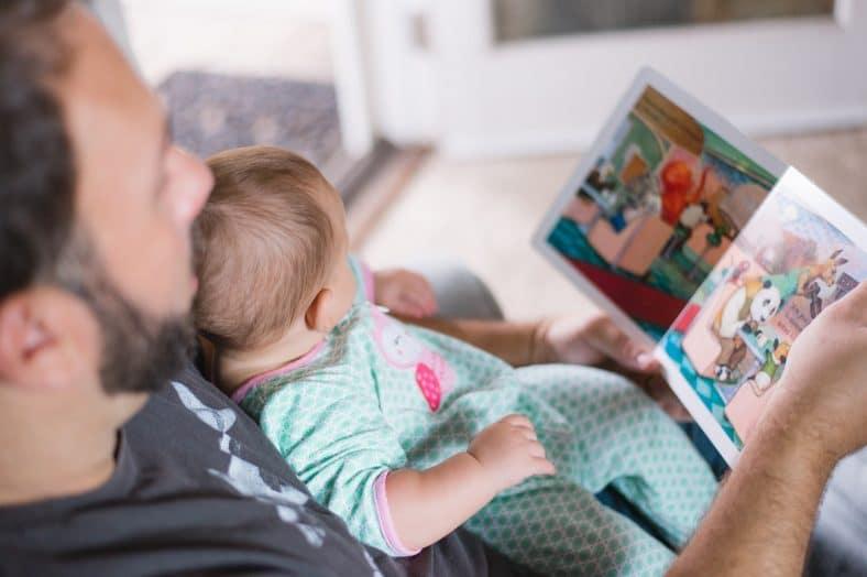 pai com criança ao colo a ler uma história no dia do pai