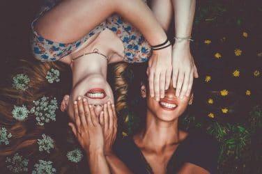 duas mulheres a taparem os olhos uma à outra deitadas num campo