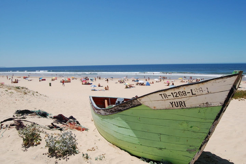 praia em lisboa, com uma lancha em primeiro plano