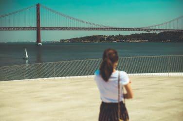 mulher na rua a olgar para a ponte 25 de abril