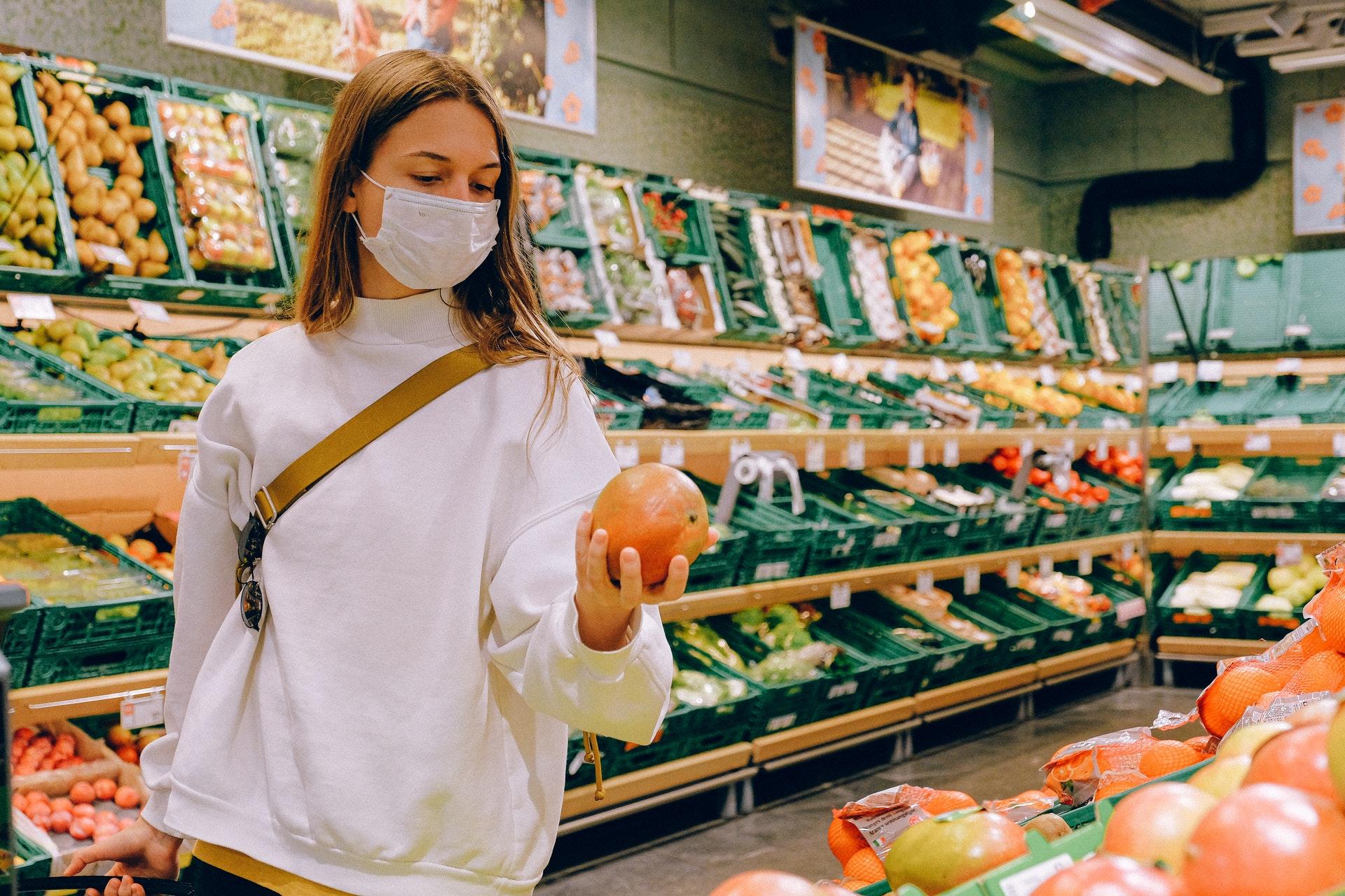 mulher de máscara num supermercado